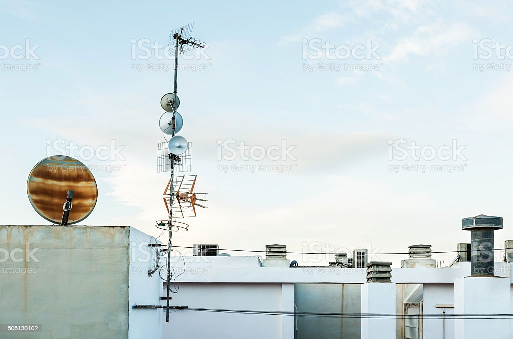 television antenna and satelite dish on white roof , Sky backgro stock photo