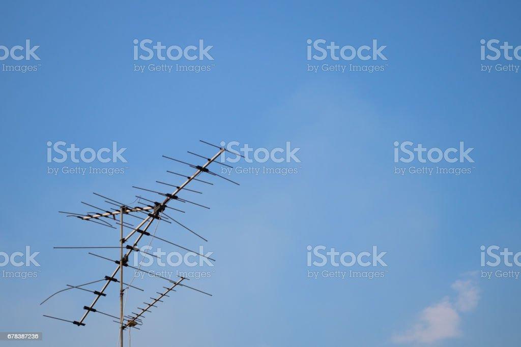Television antenna on blue sky background stock photo