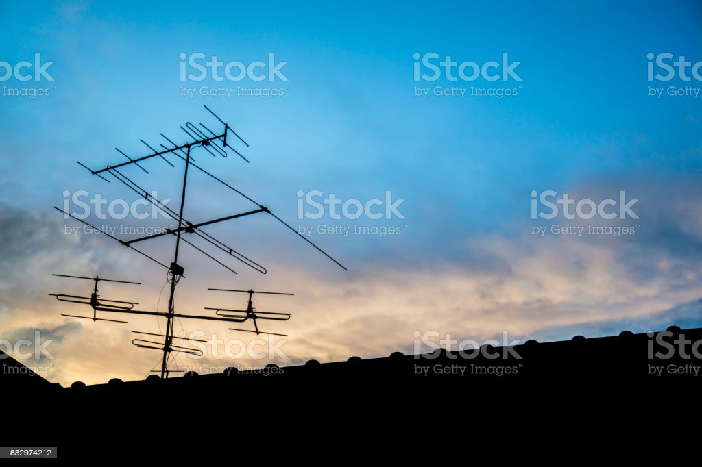 television antenna on roof with blue sky stock photo