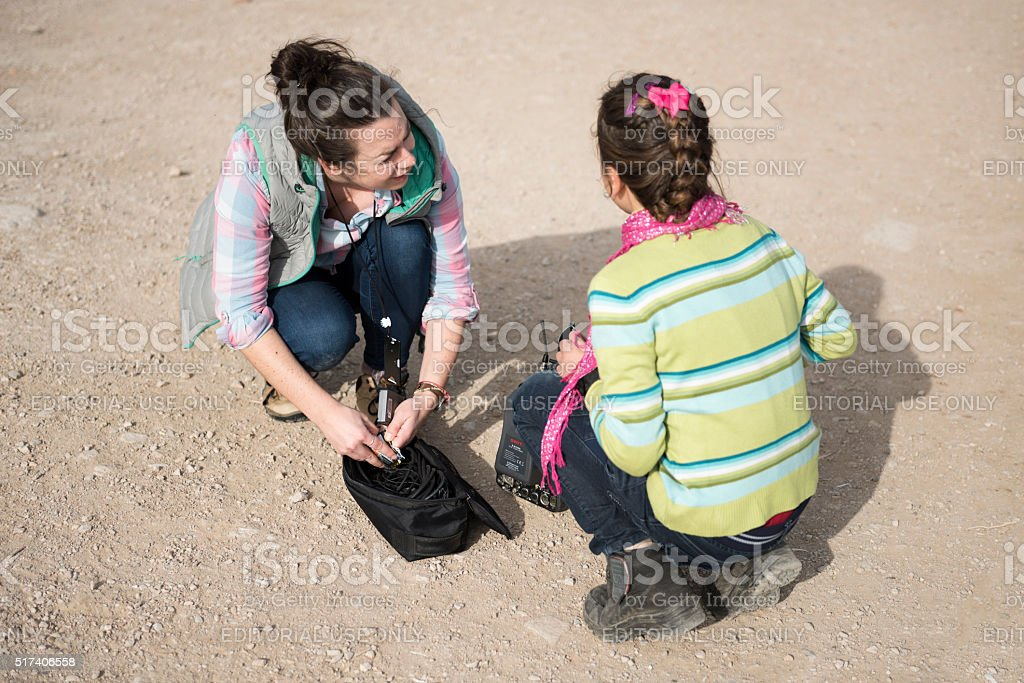 Television crew member and refugee girl communicating stock photo