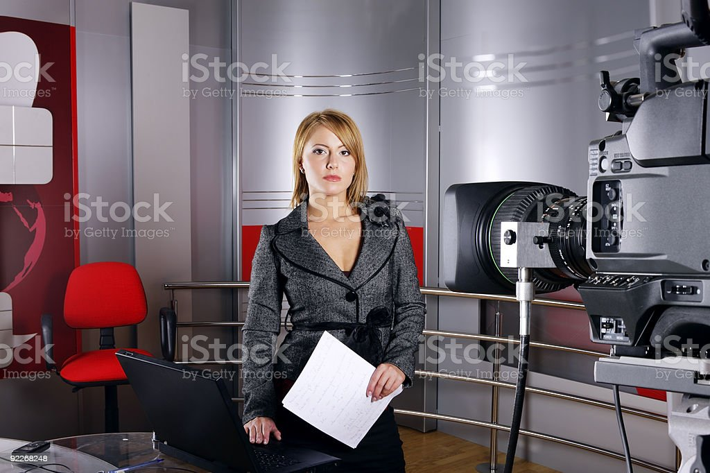 Television news reporter on a striking red and silver set stock photo