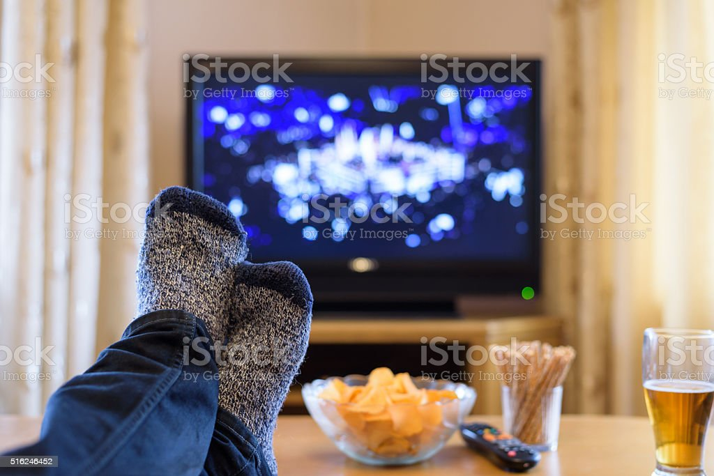 Television, TV watching (boxing match) with feet on table stock photo