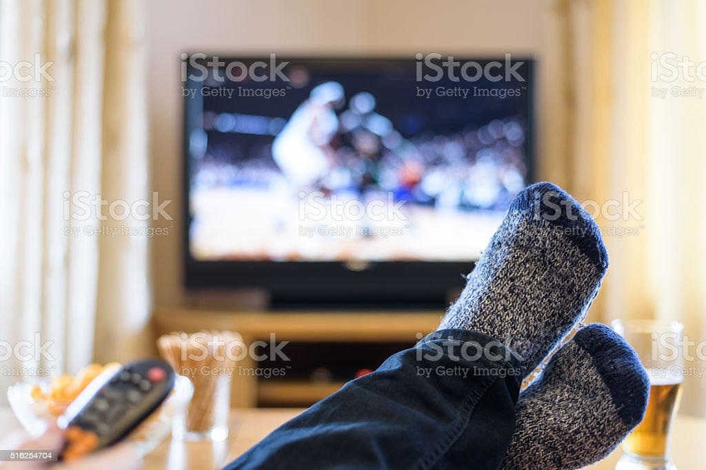 Television, TV watching (basketball game) with feet on table stock photo
