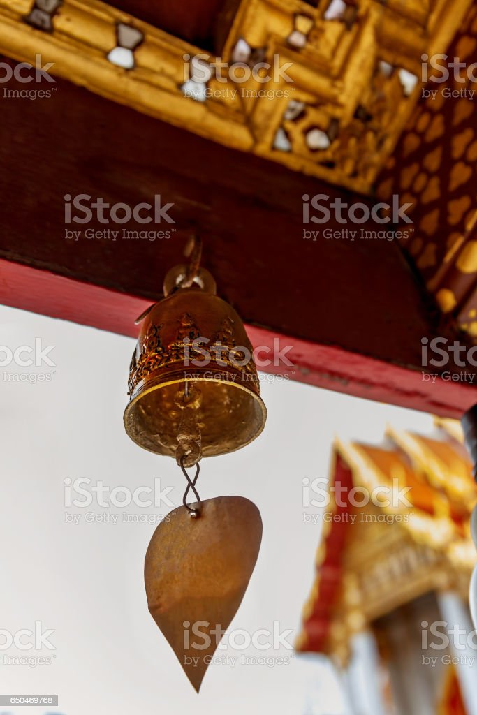 Temple bell swings in the wind in the cloisters of the Thai Buddhist temple of Wat Benchamabophit. stock photo