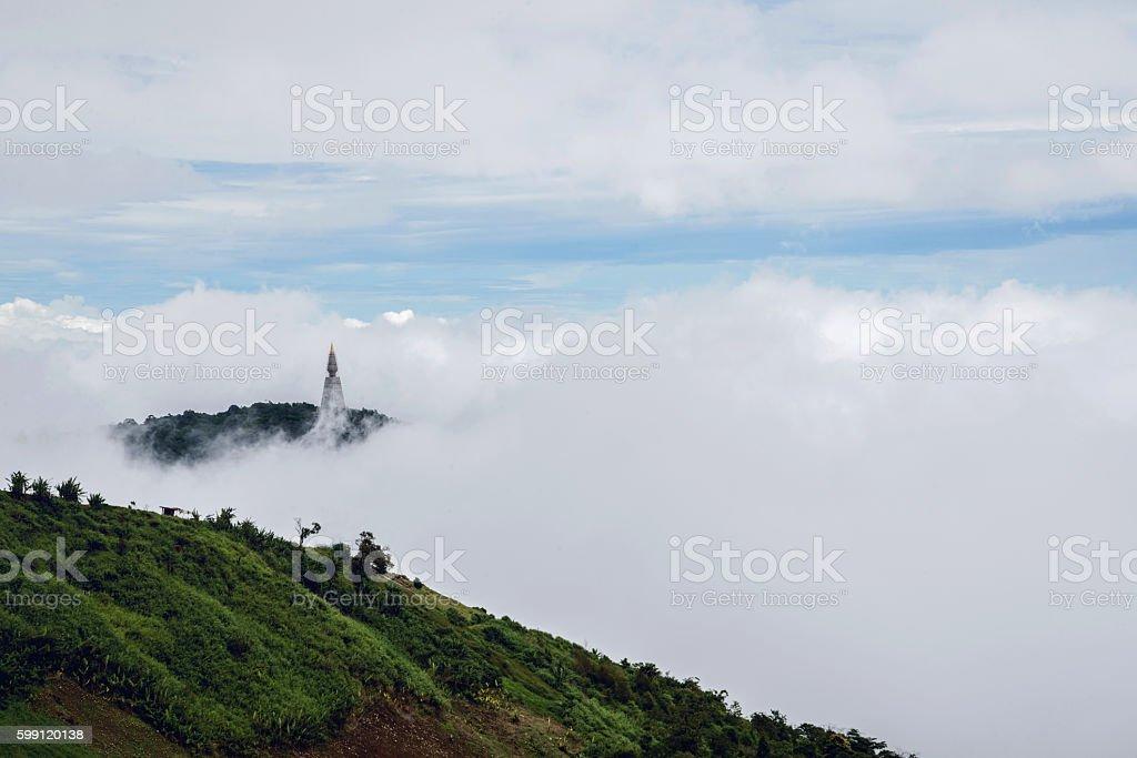 Temple pagoda atop the mist falling around him. stock photo