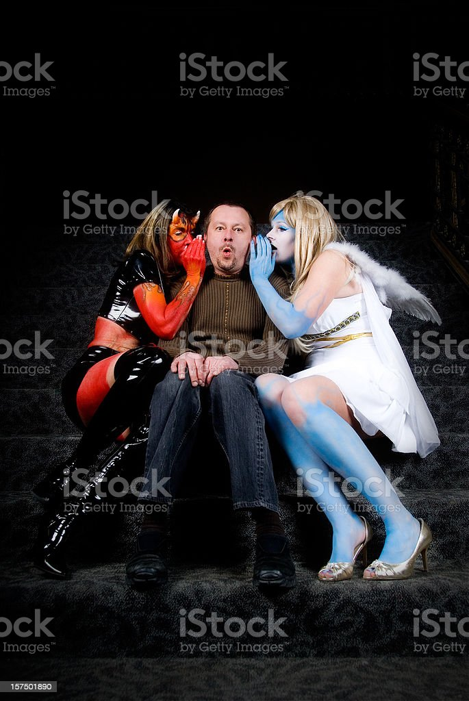 Temptations: angel and demon wispering into man's ear royalty-free stock photo