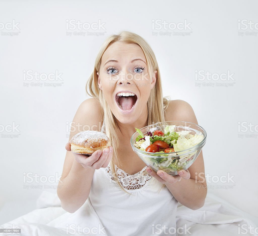 Tempted young woman making a food choice royalty-free stock photo