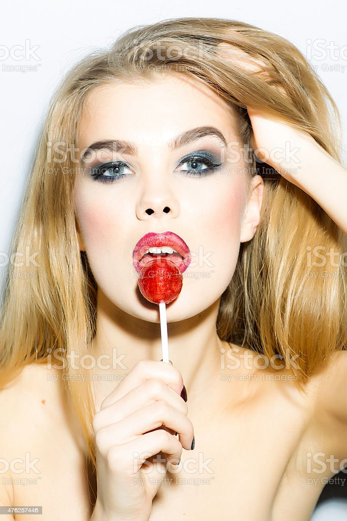 Tempting young blonde woman portrait with sugar candy stock photo