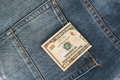 Ten American dollars bill sticking out of the blue jeans