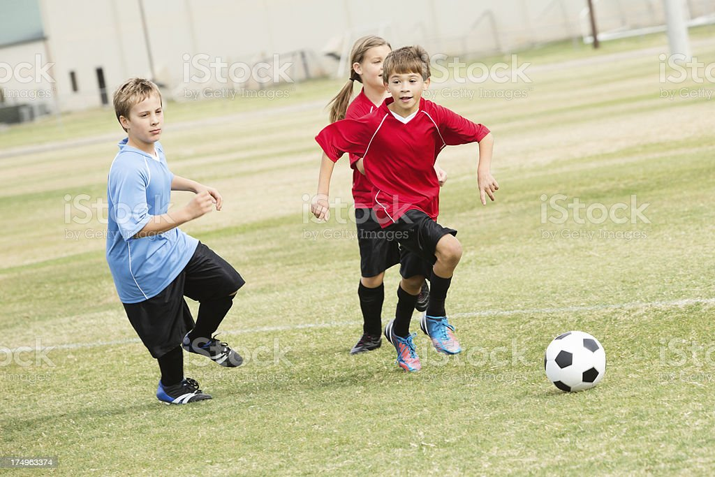 Ten and eleven year old kids playing soccer game royalty-free stock photo