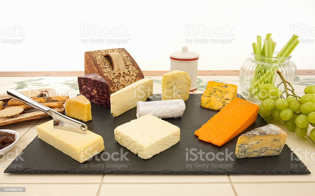 Ten different British cheeses with biscuits grapes chutney and celery stock photo