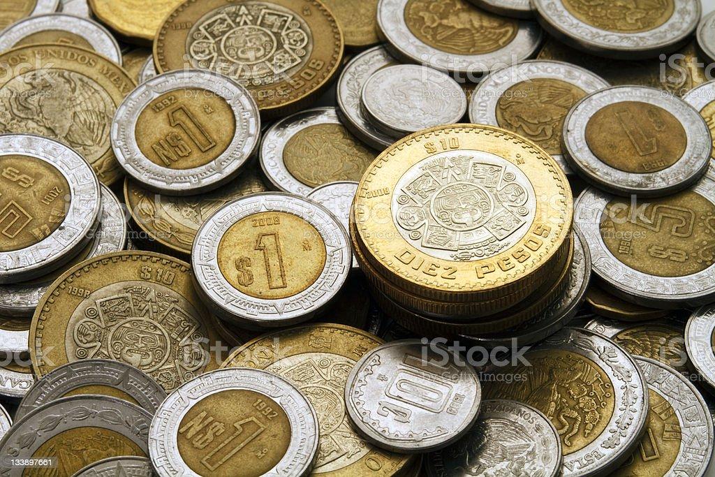 Ten Mexican Pesos Coin on a Pile of Coins stock photo