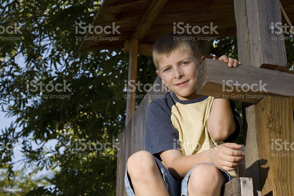 Ten year old boy in treehouse royalty-free stock photo