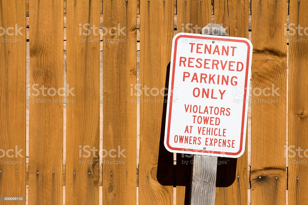 Tenant Reserved Parking Only sign and wood fence stock photo