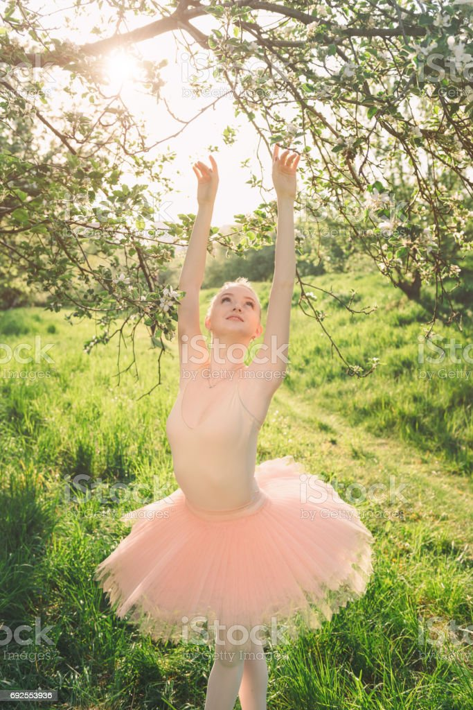 Tender and romantic dancer woman in green flowers landscape at s stock photo