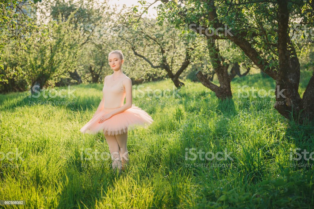 Tender and romantic dancer woman in green landscape at sunset stock photo