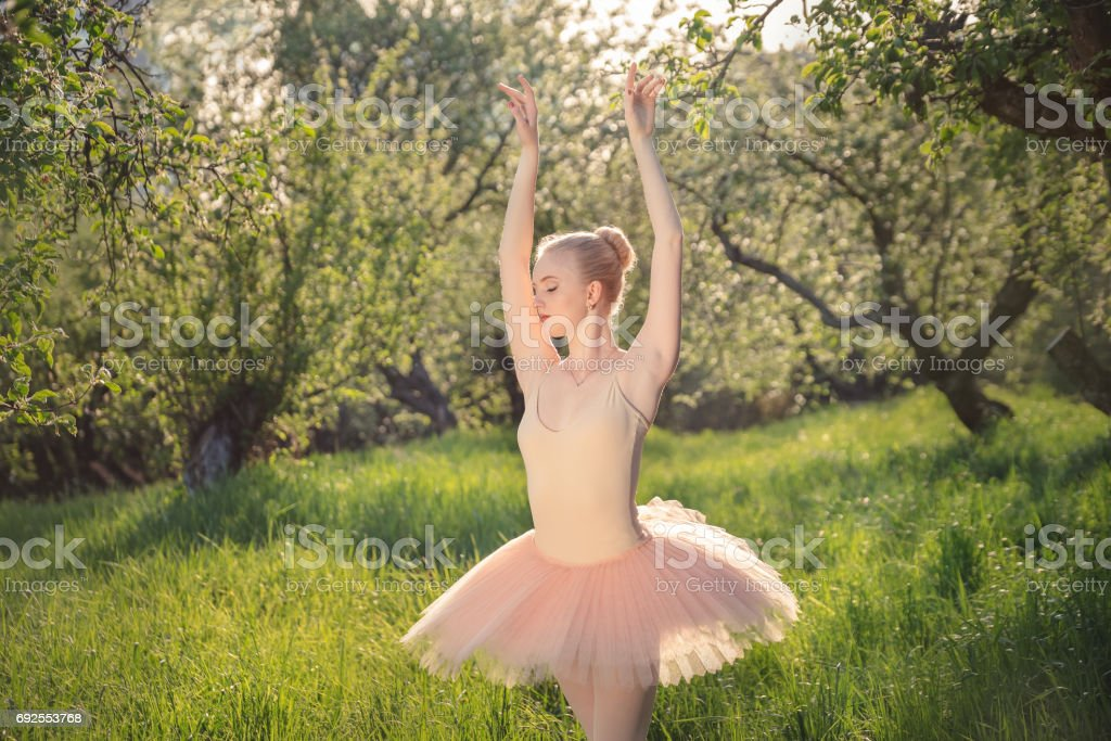 Tender dancer woman in green flowers landscape at sunset stock photo