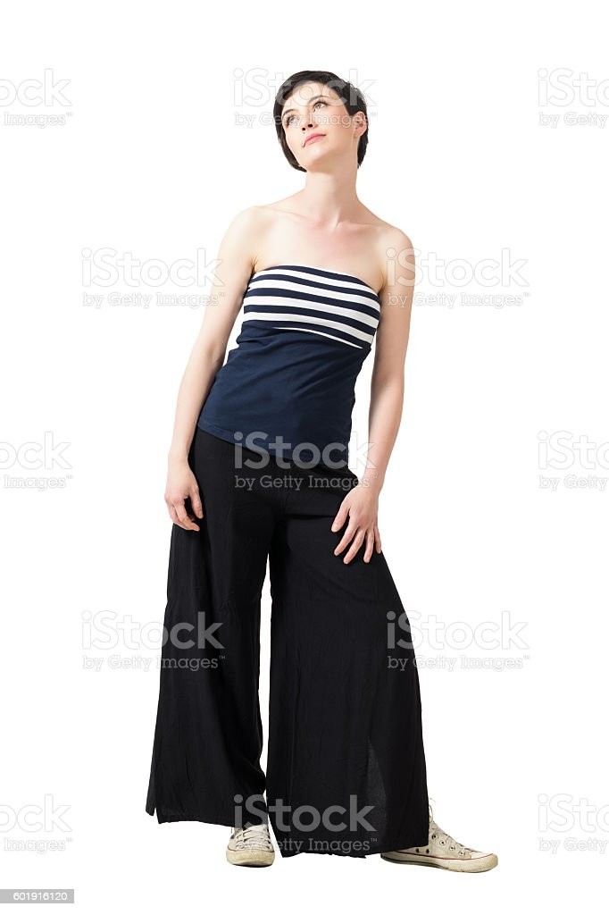Tender feminine woman in off the shoulder top looking up stock photo