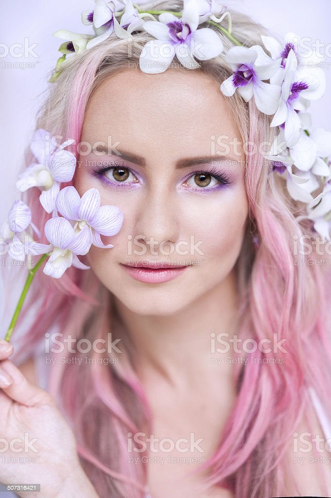 tender girl with pink hair in these orchids stock photo