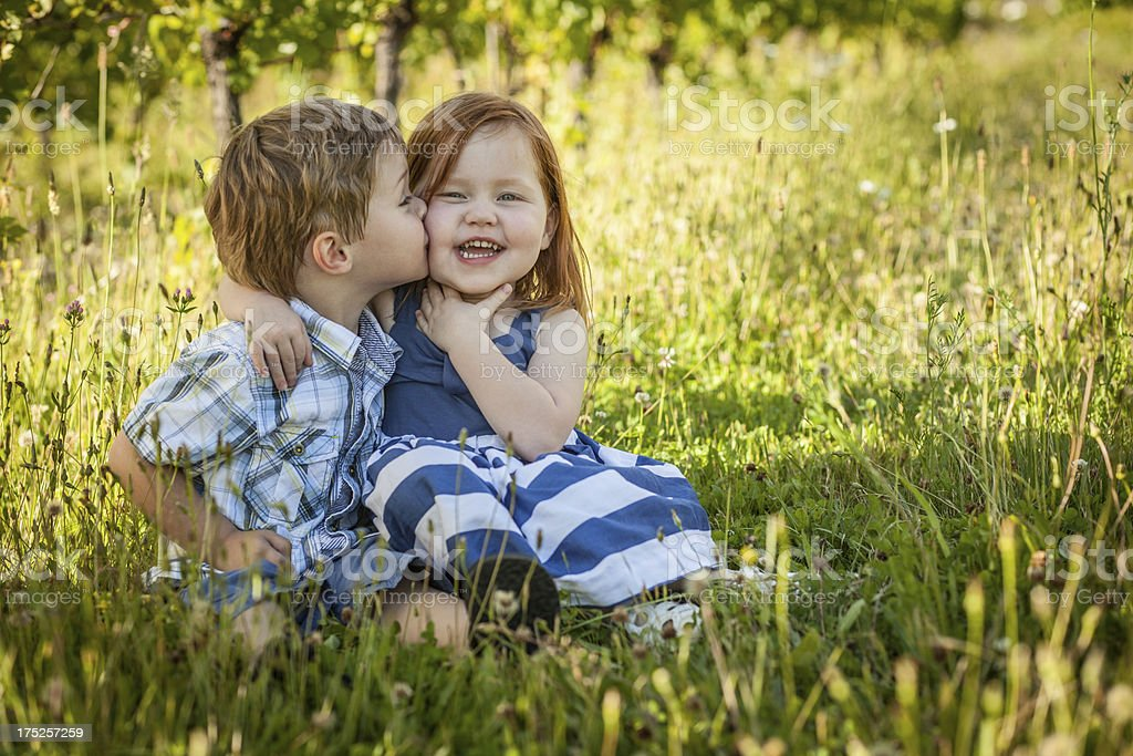 Tender kiss on check from small boy to little girl royalty-free stock photo