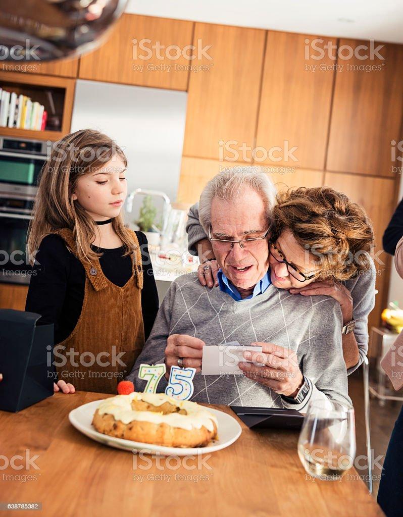 Tender moment between senior couple at birthday celebration. stock photo