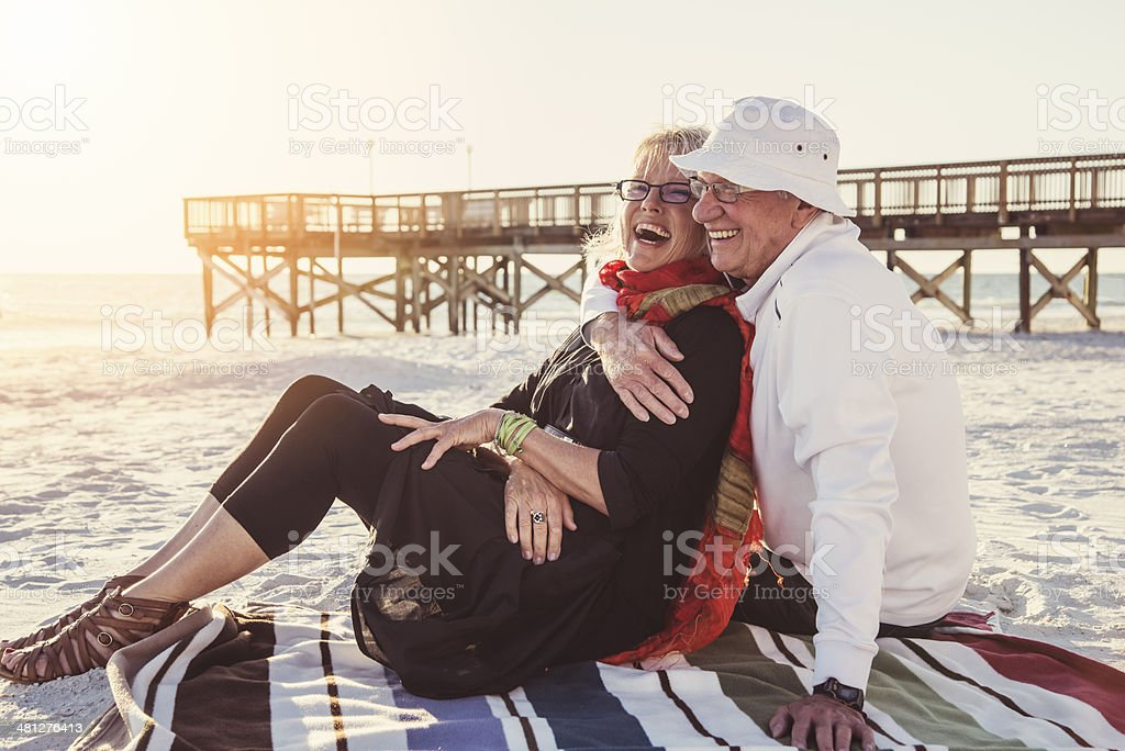 Tender moment for senior couple on the beach at sunset. stock photo