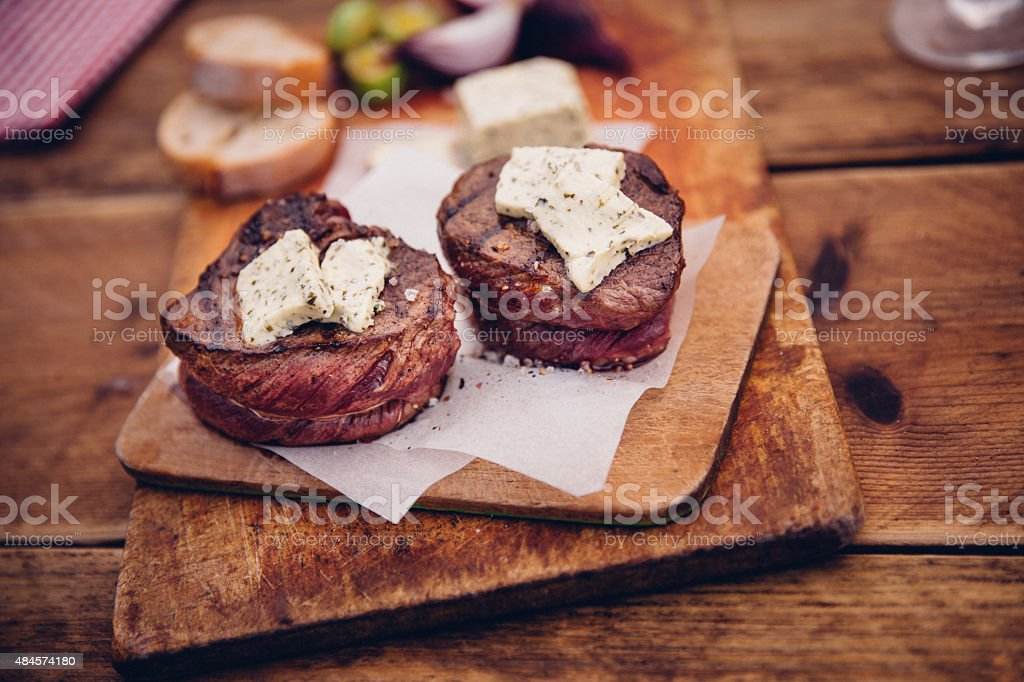 Tender steak medallions topped with cheese on wooden boards stock photo