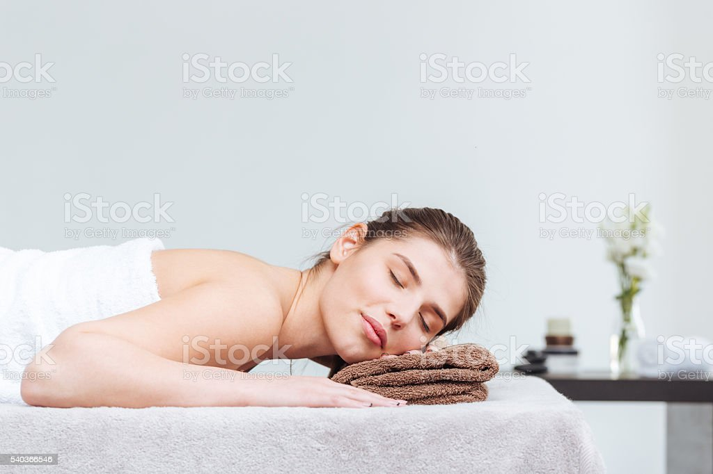 Tender woman lying during skin care treatment in spa salon stock photo