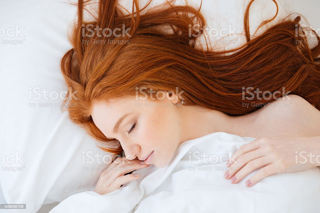 Tender woman with red hair sleeping in bed stock photo