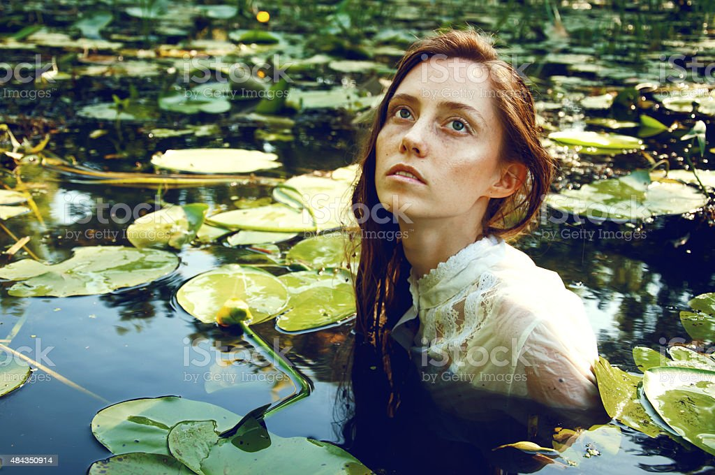 Tender young woman swimming among water lilies stock photo