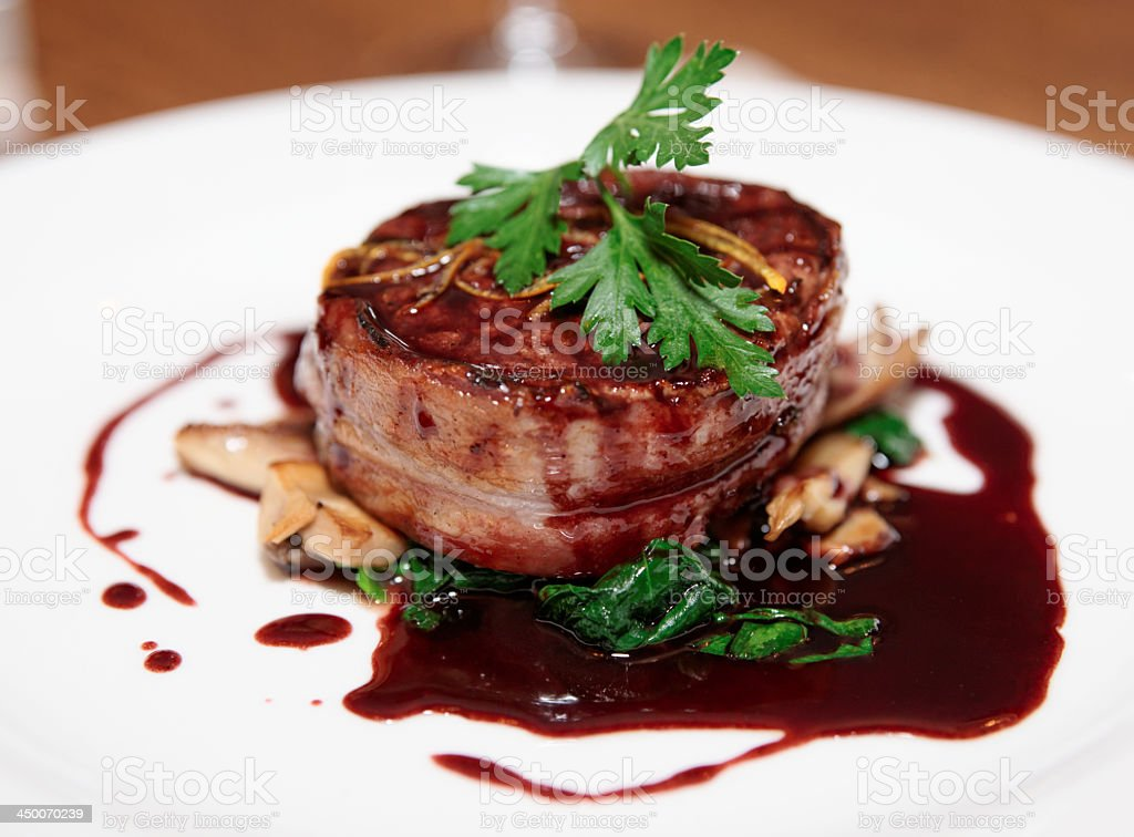 Tenderloin steak wrapped in bacon with red sauce and garlic stock photo