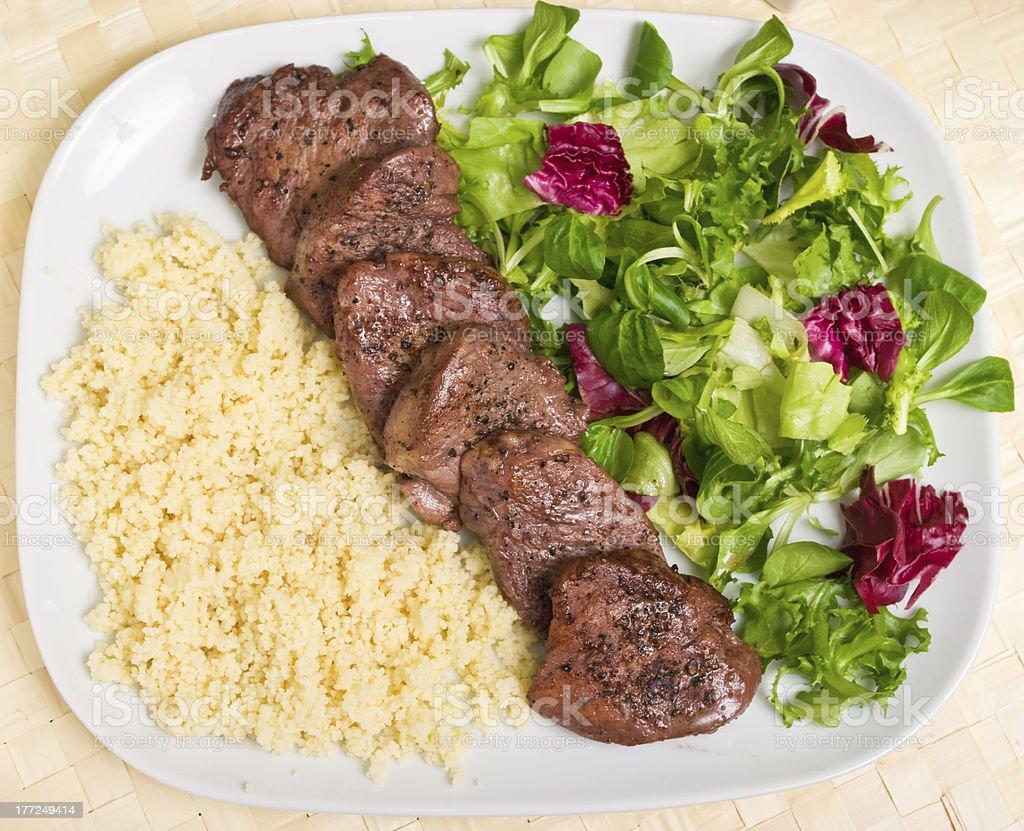 Tenderloin steaks in wine souce with kardamon and kuskus groats royalty-free stock photo