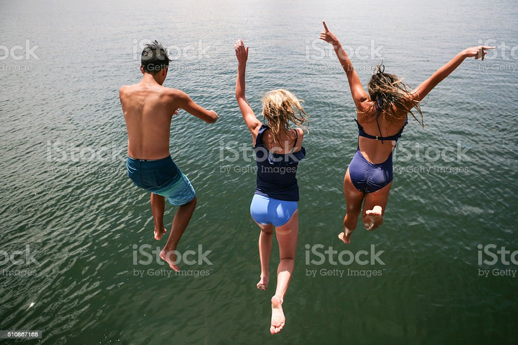 Tennagers Leaping into Lake stock photo