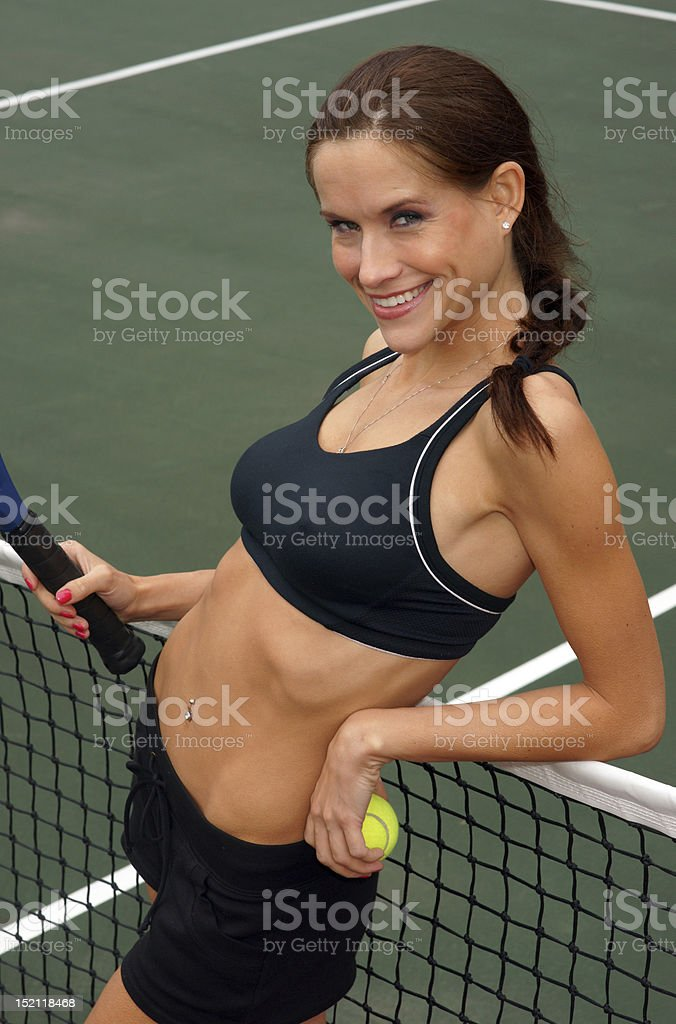 Tennis Anyone Sensual Female Player Leans against The Net royalty-free stock photo