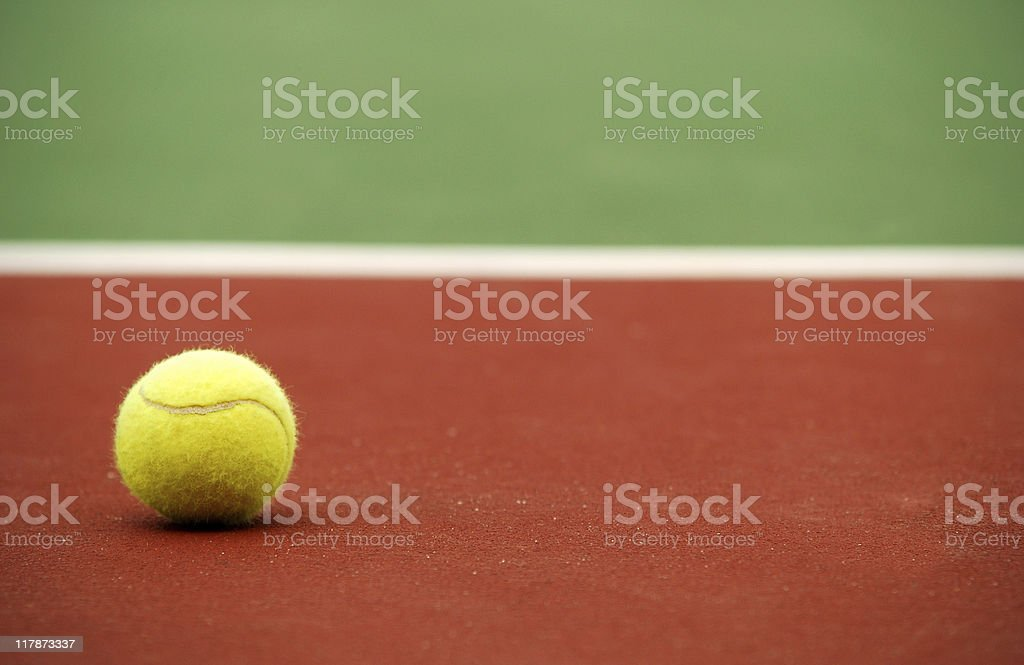 A tennis ball alone on a court background royalty-free stock photo