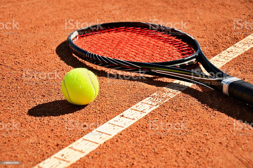 tennis ball and racket is on the carpet court horizontal stock photo