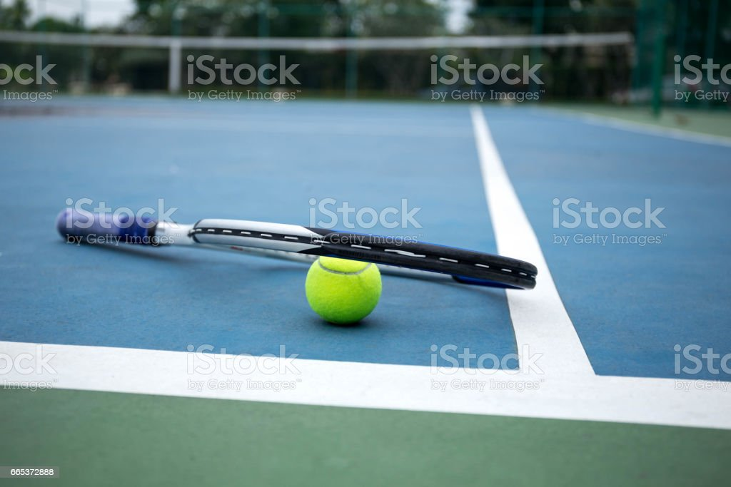 Tennis Ball and Racket on tennis court stock photo