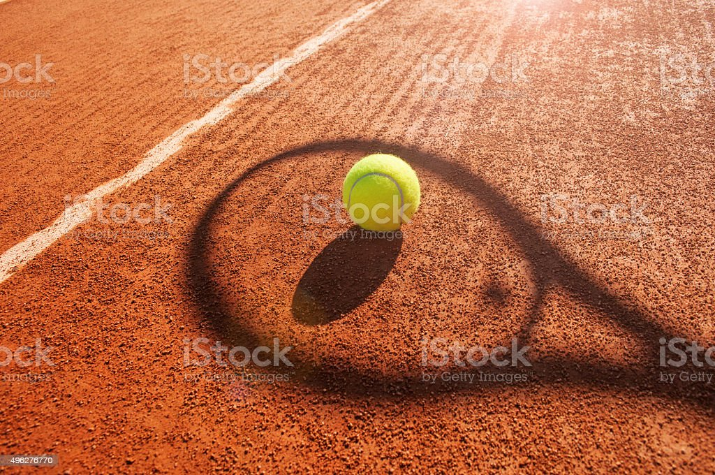 Tennis ball and racket shadow on clay court.