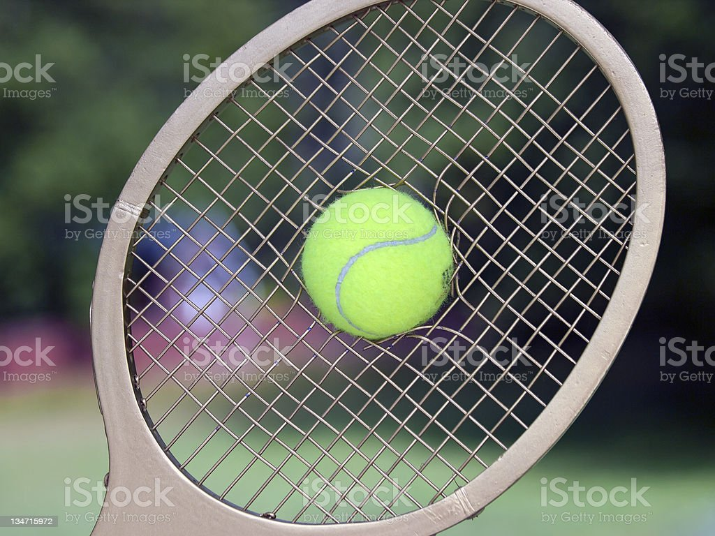 Tennis Ball Breaks Through Racquet Strings royalty-free stock photo