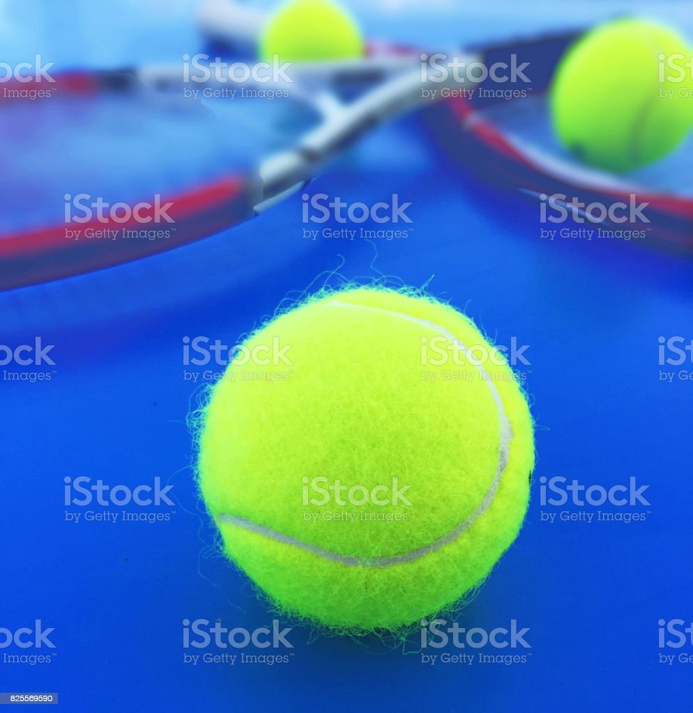 Tennis Ball close up and two tennis rackets with two balls in the background. stock photo