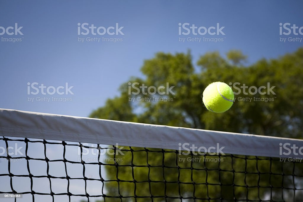 A tennis ball going over a tennis net royalty-free stock photo