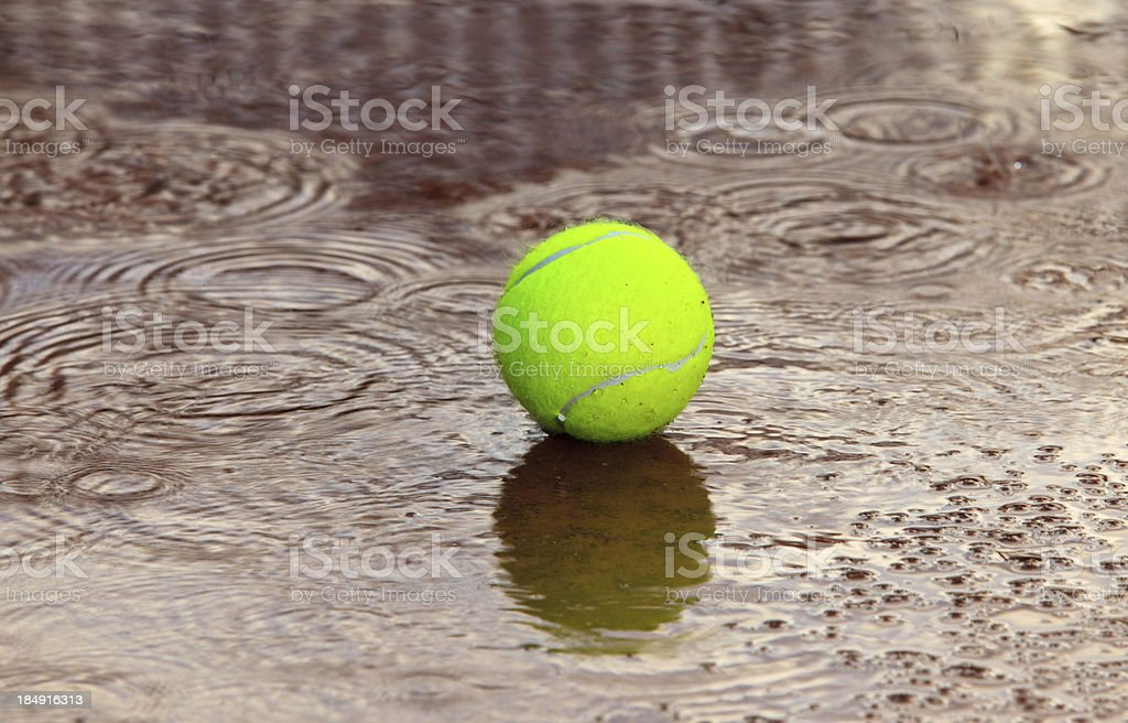 Tennis ball  in a rain puddle stock photo