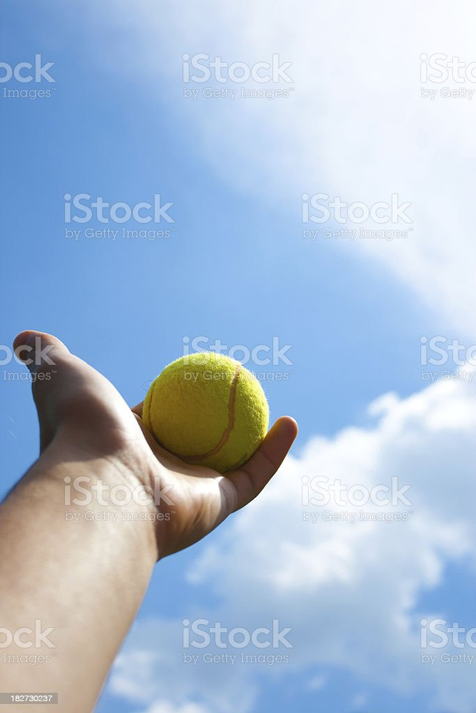 Tennis ball in hand against a blue sky royalty-free stock photo