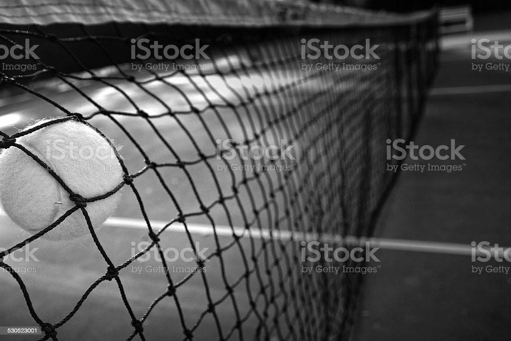 Tennis ball in net B & W stock photo