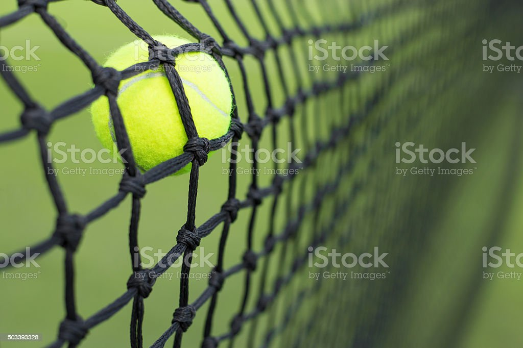 Tennis ball in the net stock photo