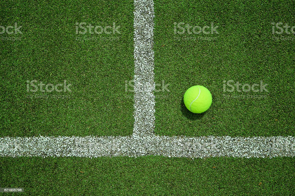 Tennis ball near the line on tennis grass court stock photo