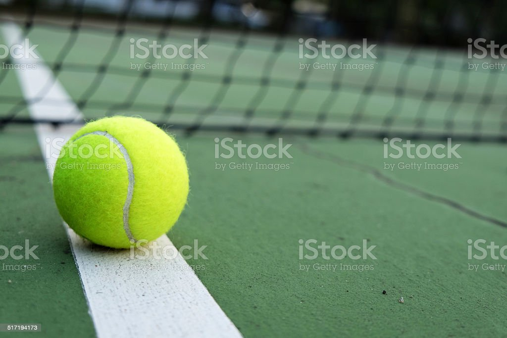 tennis ball on green court stock photo