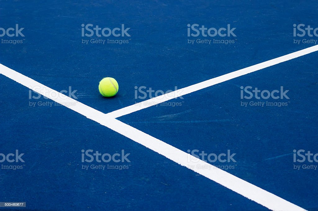 Tennis ball on tennis court. Blue hard surface. stock photo