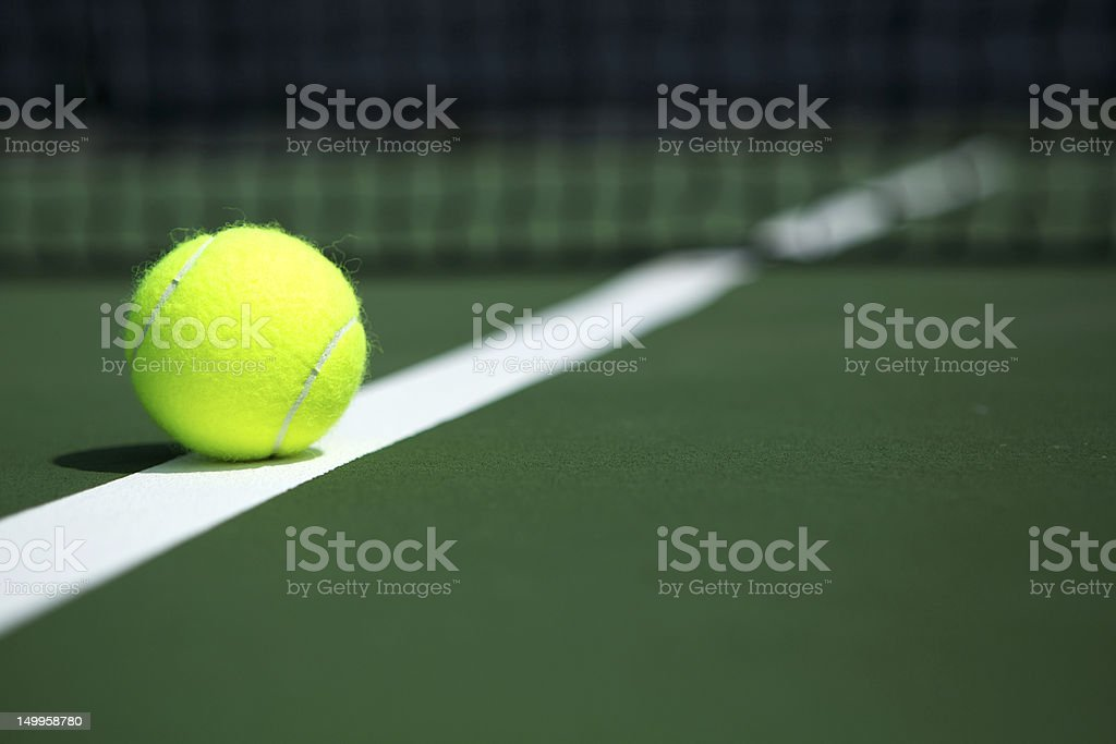 Tennis Ball on the Court with the Net in the background