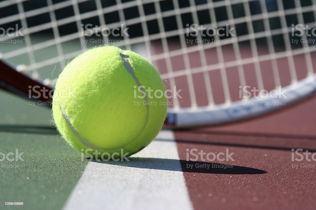 Tennis Ball on the court with racket in background royalty-free stock photo